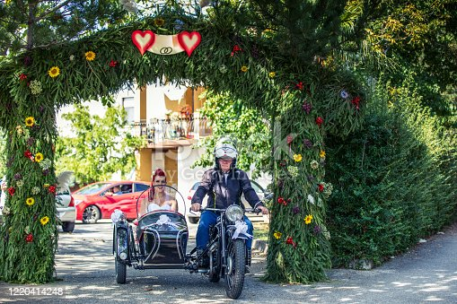 Bride Leaving Her House in an Old-fashioned Sidecar Motorcycle and Going To Wedding Ceremony.