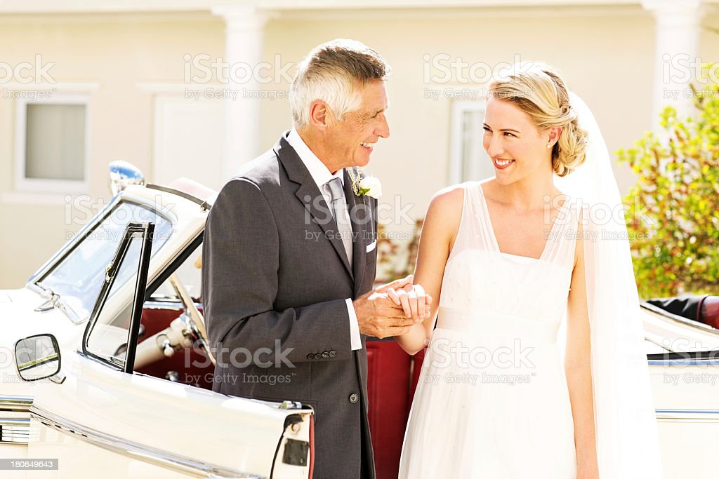 Bride Looking At Father While Standing By Wedding Car stock photo