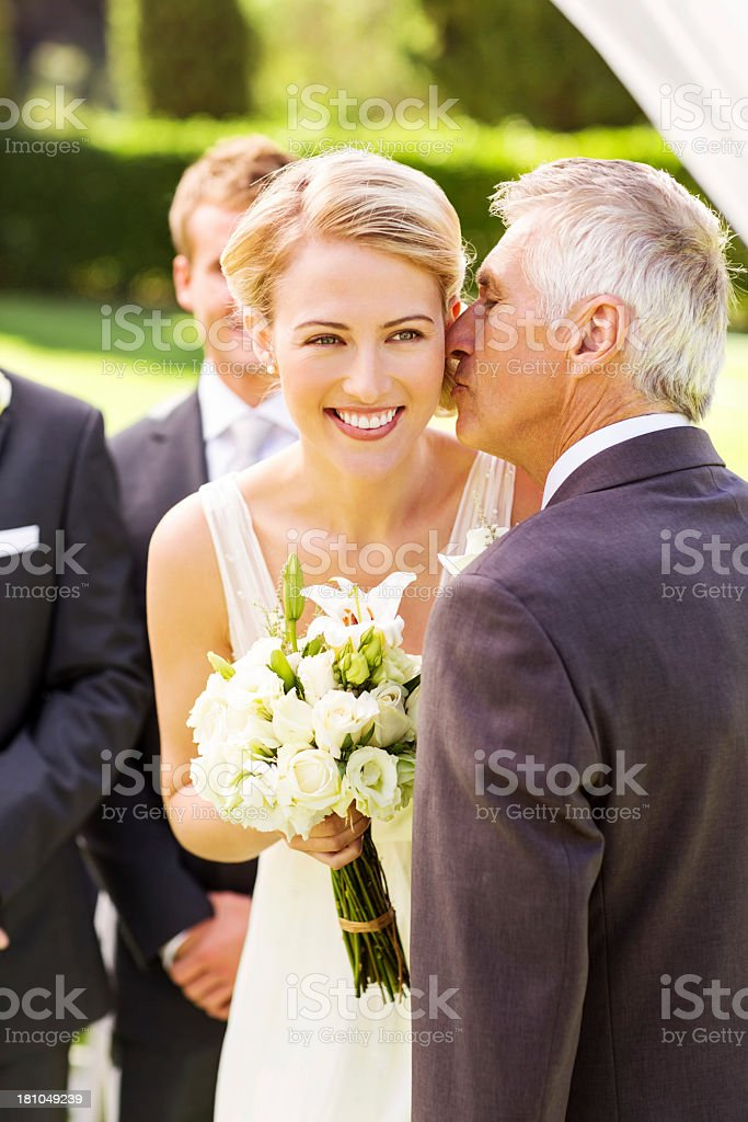 Bride Looking Away While Father Kissing Her On Cheek stock photo