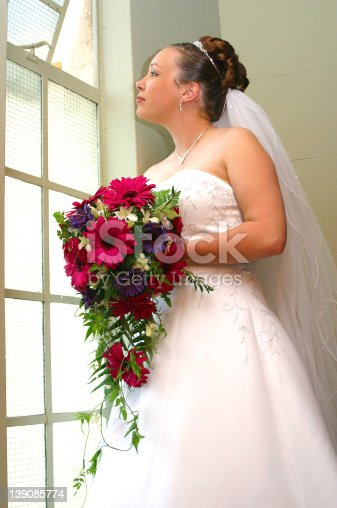 Photograph of a bride with flowers looking out the window.