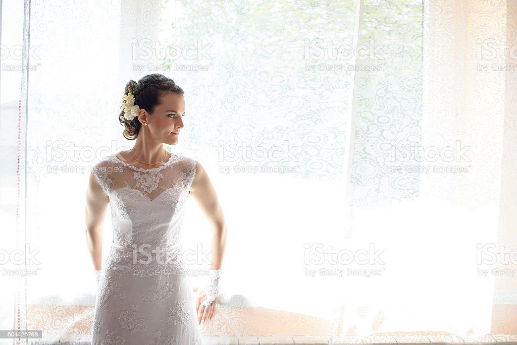 Bride looking through the window stock photo