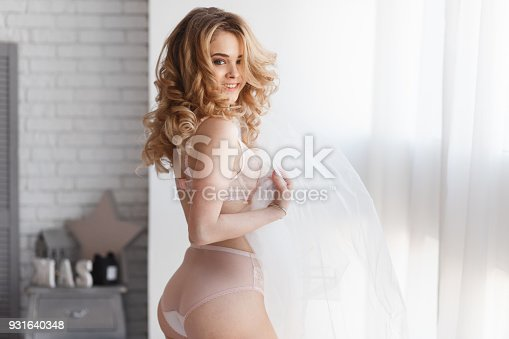 Bride morning preparation. Beautiful bride in white wedding negligee and veil on the background of large bedroom window. Horizontal view.