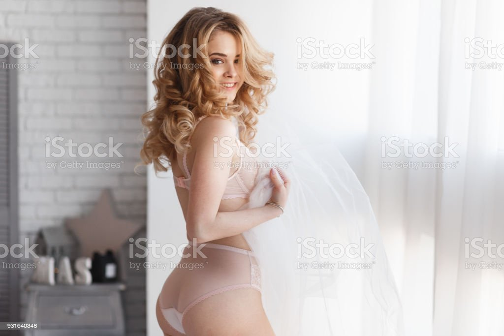 Bride morning preparation. Beautiful bride in white wedding negligee and veil on the background of large bedroom window. Horizontal view stock photo