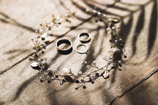 istock Bride necklace and wedding rings on wooden texture, view from above 1010488106