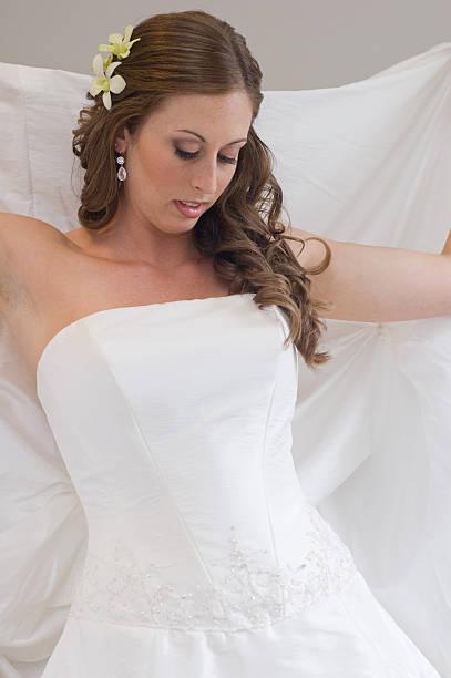 braut im weißen hochzeitskleid putting ihre schleier - hochzeits make up blaue augen stock-fotos und bilder