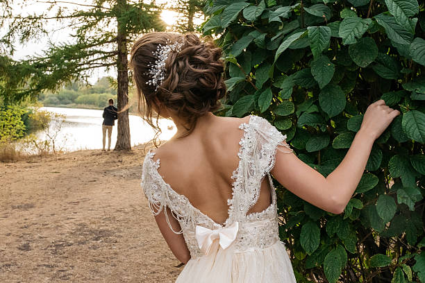 Bride peeking out from behind a tree stock photo