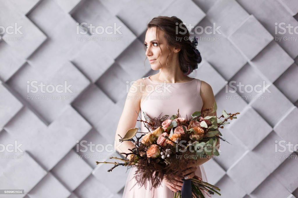 Bride portrait. Young beautifull woman holding bouquet on geometric gray background in studio stock photo