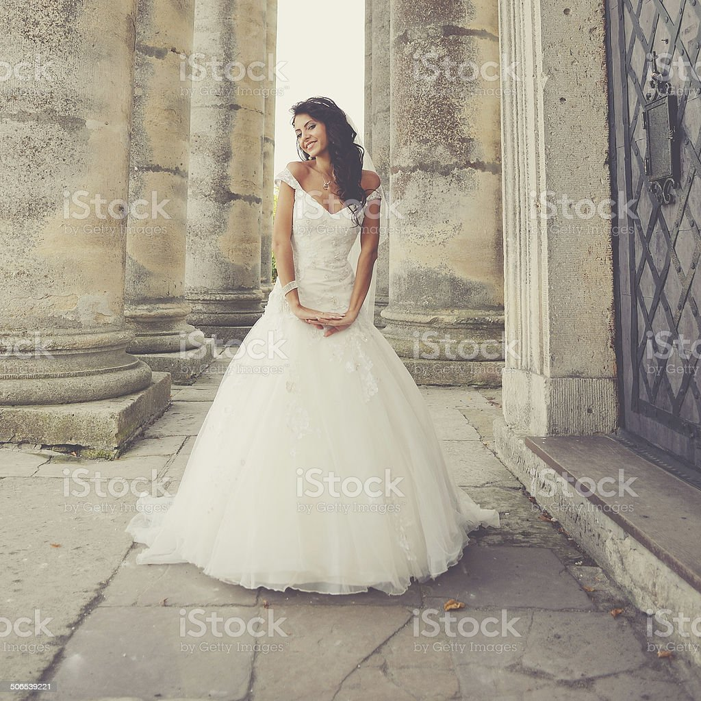 bride posing on the steps of an old church stock photo