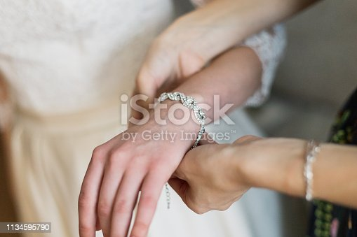 istock bride putting on luxury bracelet on hand in the morning, getting ready 1134595790
