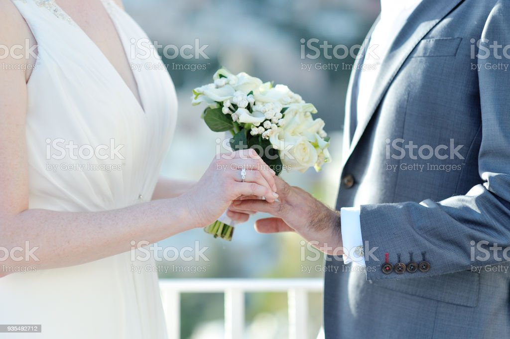 Bride putting wedding ring on groom's finger in wedding day stock photo