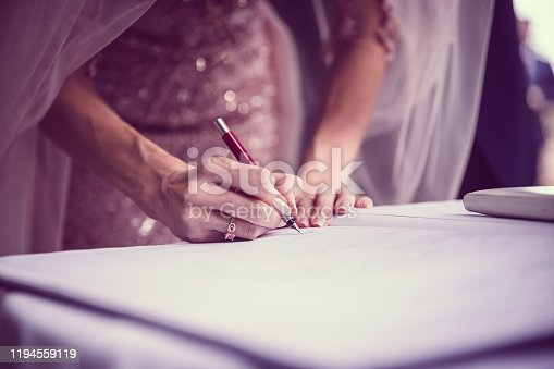 New bride signing paperwork. Hands signing during the wedding