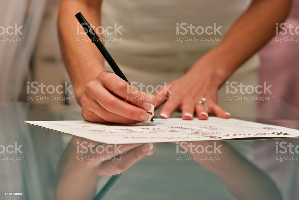 Bride Signing Wedding Certificate Reflection on Glass Table stock photo