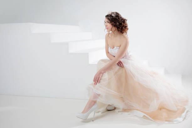 La novia se sienta en las escaleras. Retrato de una hermosa muchacha en un vestido de novia. Bailando el fondo de la novia, blanca. - foto de stock