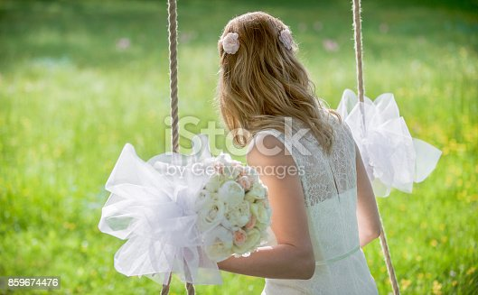 Bride sitting on swing in park.