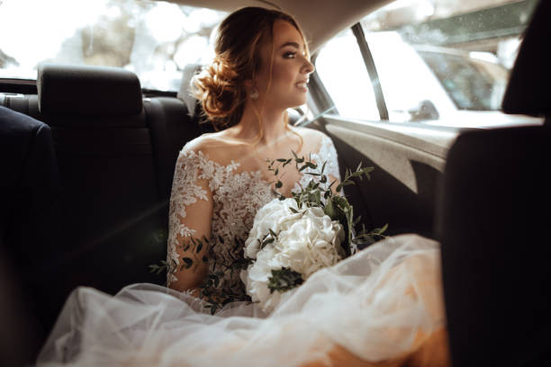 Bride sitting in the backseat stock photo