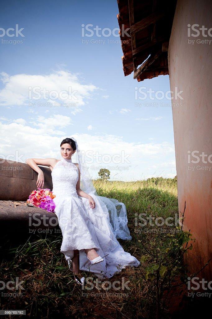 Bride Sitting on Sofa Outside Old Farm House and Bouquet - foto de acervo