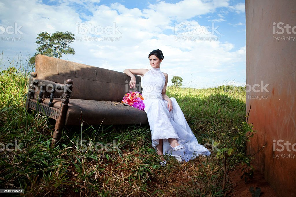 Bride Sitting on Sofa Outside Old Farm House and Bouquet foto royalty-free