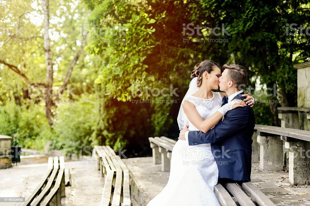 Bride sitting on the groom's knees and kisses him stock photo