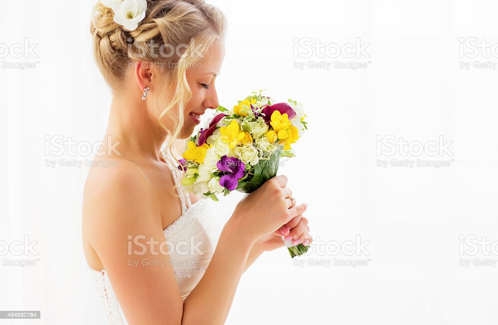 Bride smelling her wedding bouquet stock photo