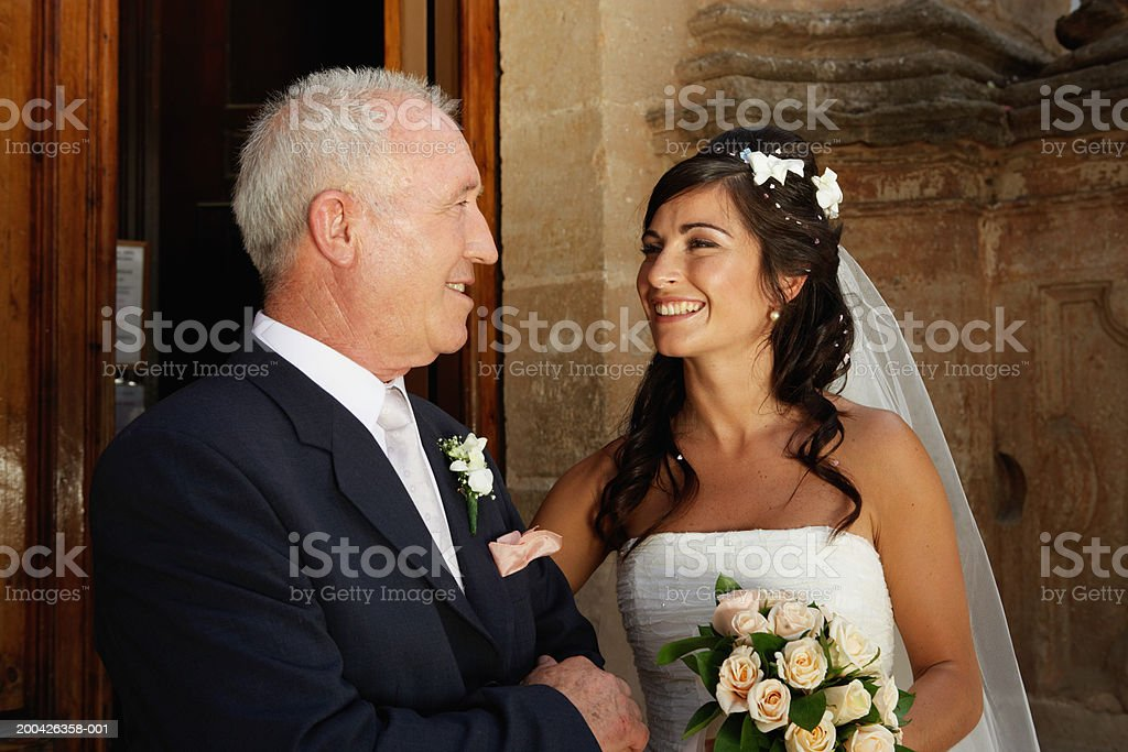 Bride smiling at father stock photo
