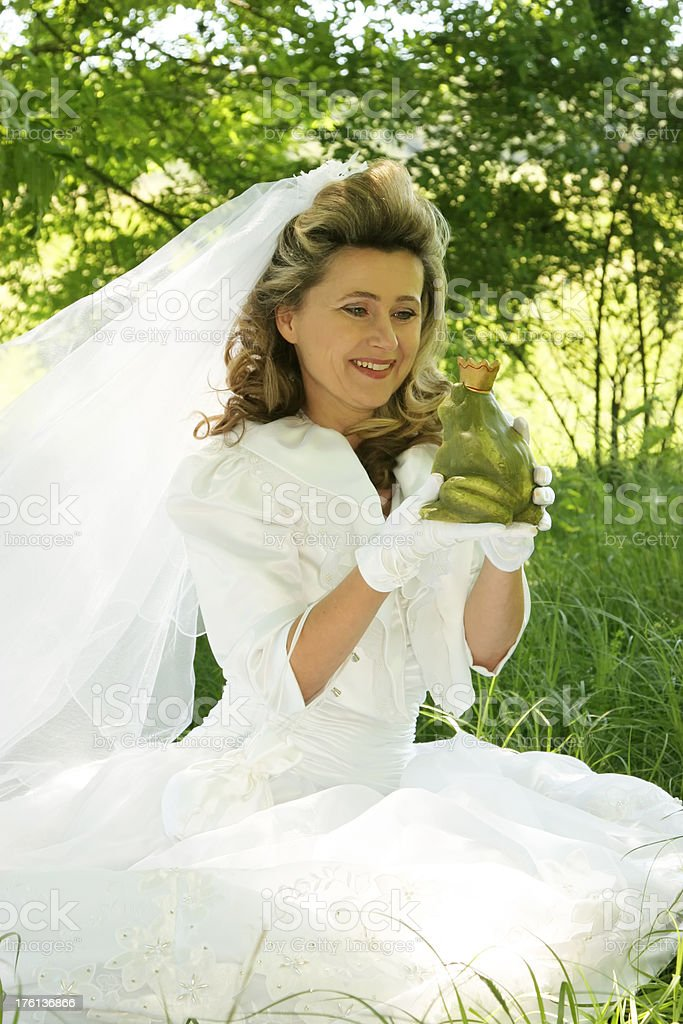 bride smiling at  frog prince stock photo