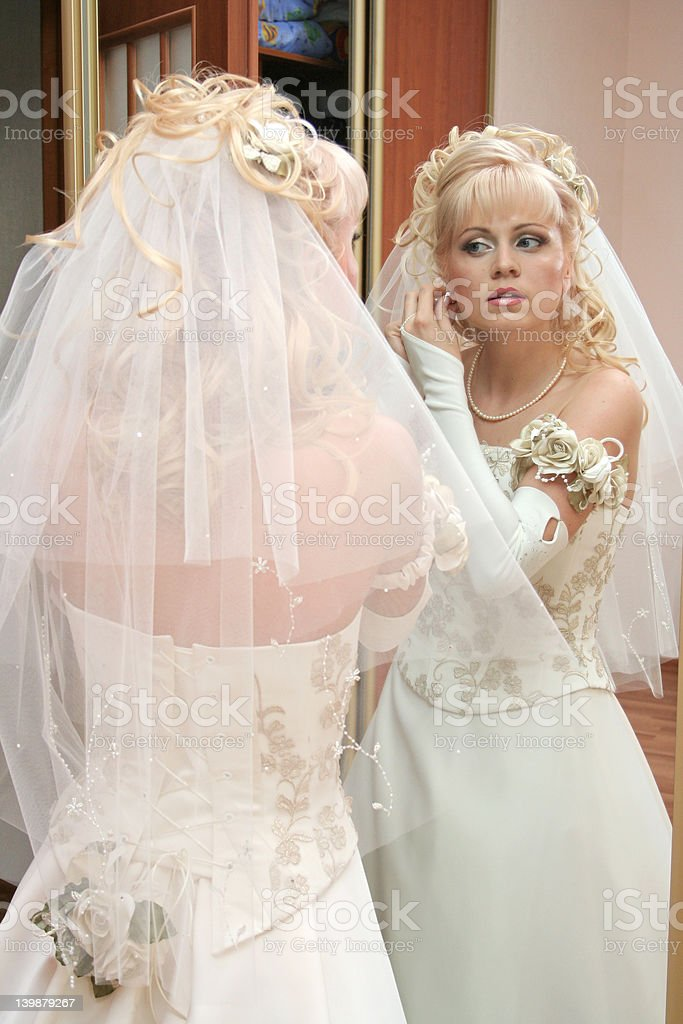 Bride stand before mirror royalty-free stock photo