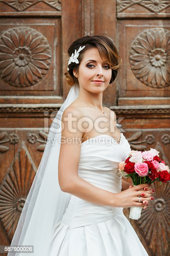 Wedding photo shooting. Bride standing near wooden door. Wearing white dress and veil and holding bouquet. Outdoor