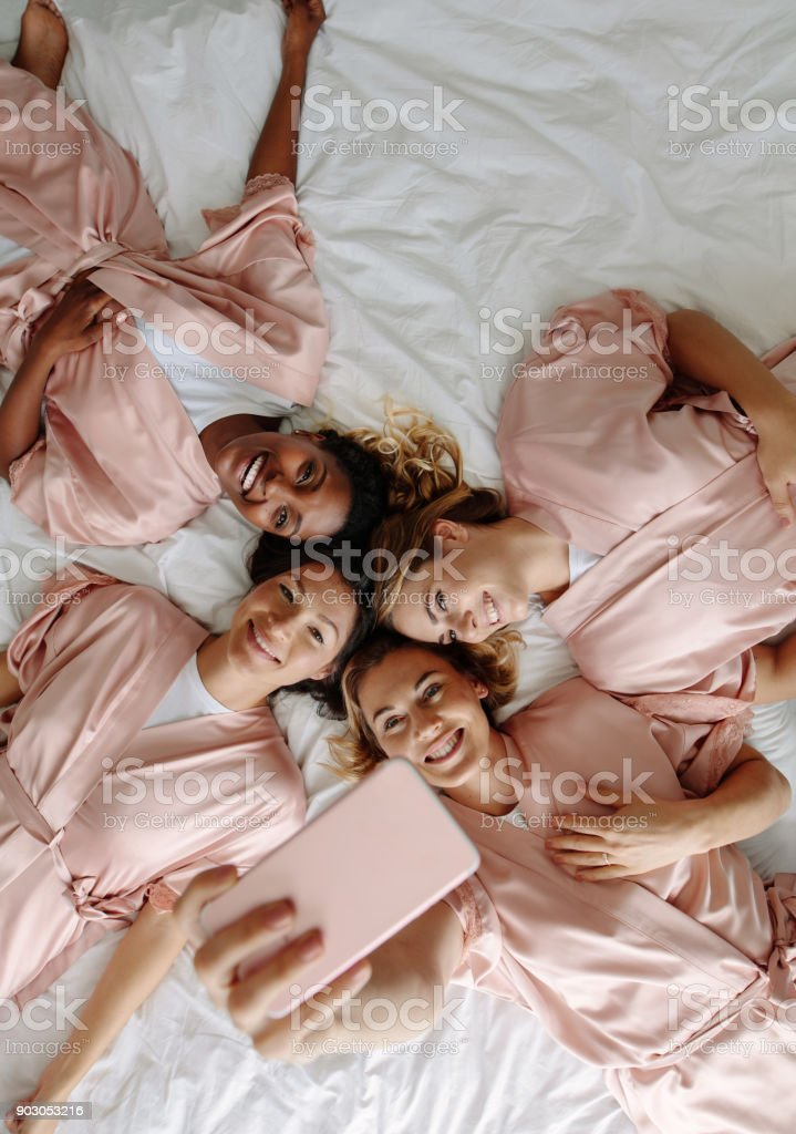 Bride taking selfie with bridesmaids while lying on bed stock photo
