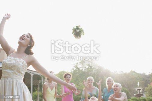 istock Bride throwing bouquet at wedding reception 102284216