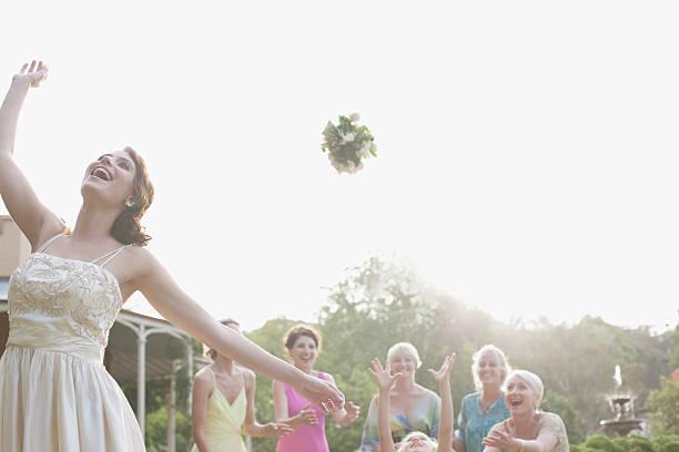 braut werfen bouquet an hochzeitsempfang - hochzeitsblumensträuße stock-fotos und bilder