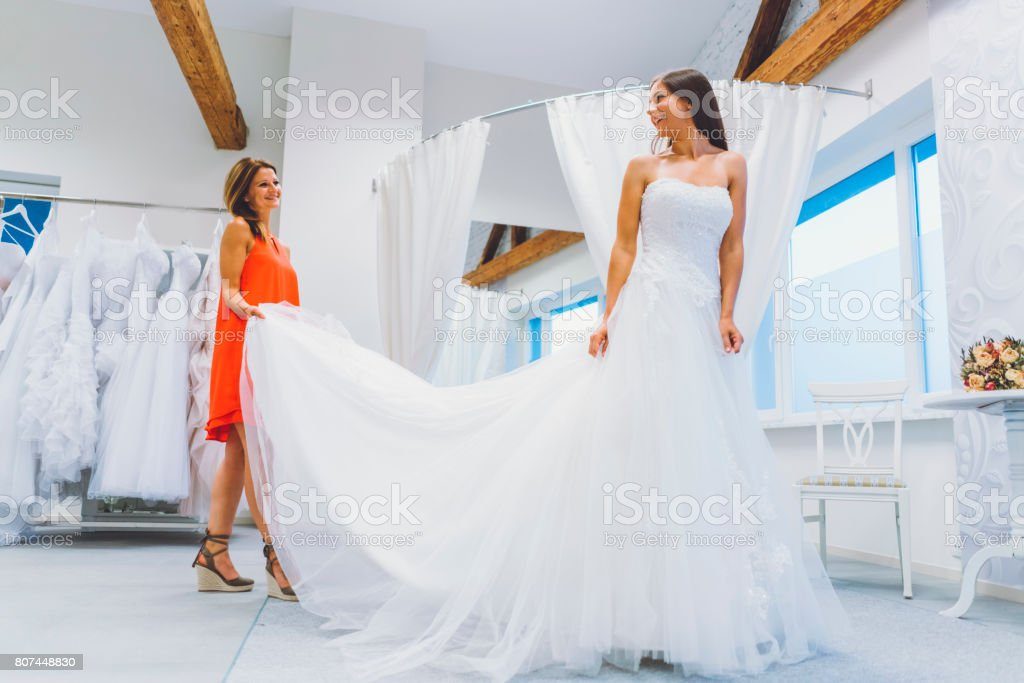 Bride to be choosing her perfect wedding dress stock photo