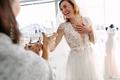 Cheerful young woman in wedding gown toasting champagne with friends in bridal Boutique. Beautiful bride in elegant wedding dress clinking glasses of champagne with her friends and smiling in wedding fashion shop.