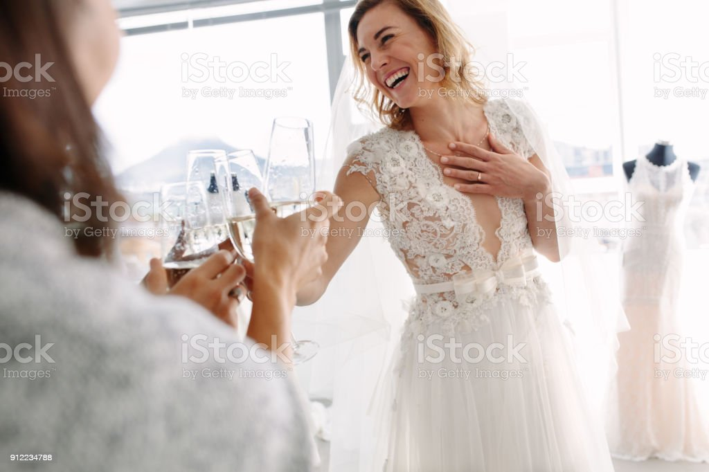 Bride toasting champagne with friends in bridal boutique stock photo