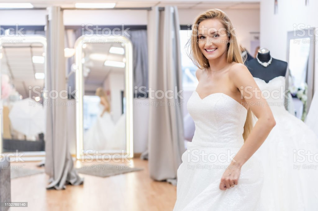 Bride Trying On Wedding Dress At Store Stock Photo