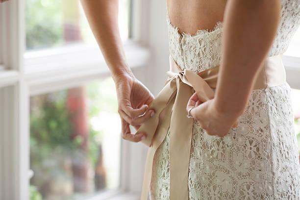 Bride Tying Wedding Dress stock photo