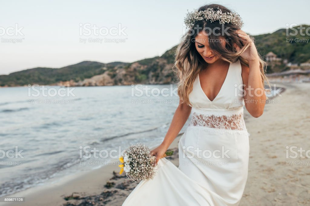 Bride walking on the beach stock photo