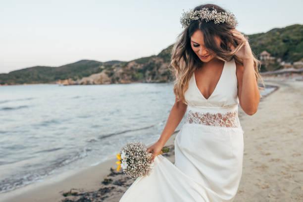 Bride walking on the beach stock photo