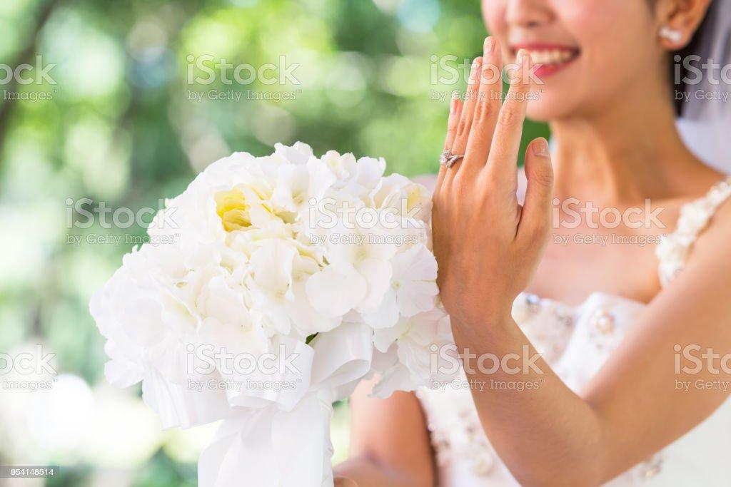 6bc88723d4b32 Braut trägt Hochzeit Kleid Lächeln zeigt Ehering und halten Blumenstrauß  Gefühl so stolz und Glück in