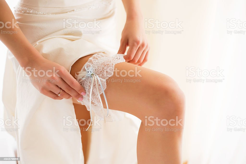 Bride wearing wedding garter stock photo