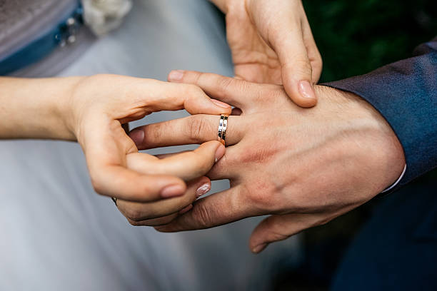 Bride wears the ring on the finger of the groom stock photo