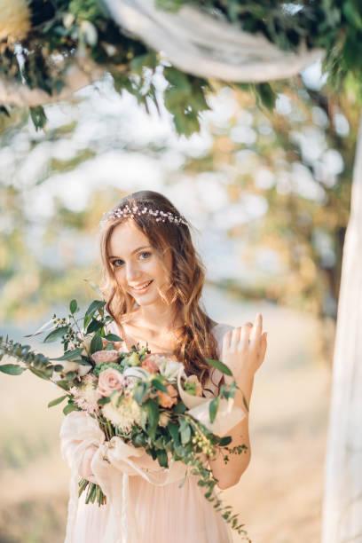 braut mit bouquet von blumen - hochzeitsfrisur twilight stock-fotos und bilder