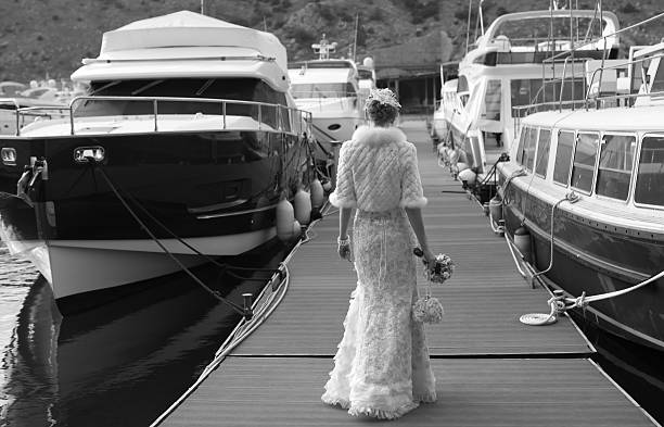 Bride with bouquet walking on pier near  yacht. stock photo