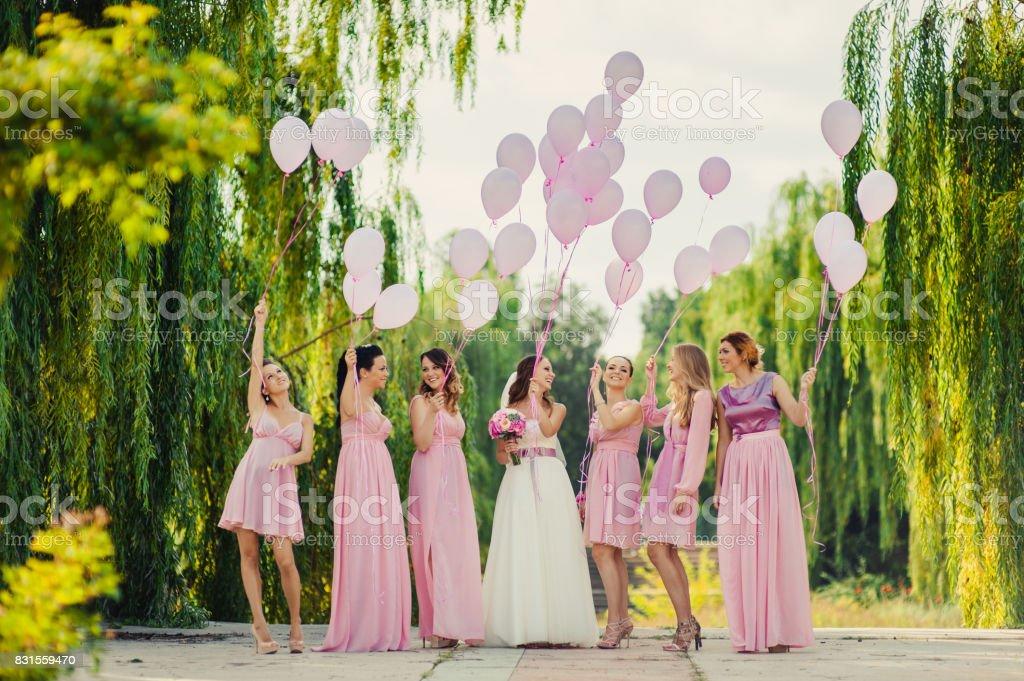 Braut mit Brautjungfern in rosa Kleider für einen Spaziergang – Foto