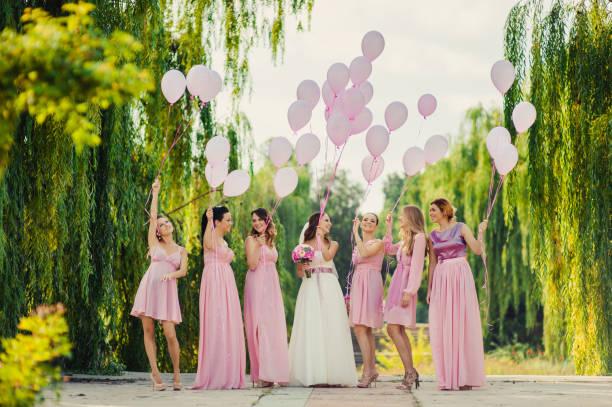 braut mit brautjungfern in rosa kleider für einen spaziergang - kleid mit verzierung stock-fotos und bilder