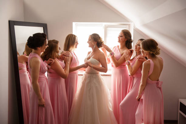 Bride with bridesmaids posing in hotel or fitting room at wedding day stock photo