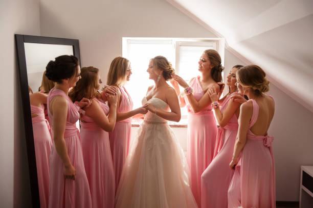 braut mit brautjungfern posieren in hotel oder umkleidekabine am hochzeitstag - verlobungskleider stock-fotos und bilder