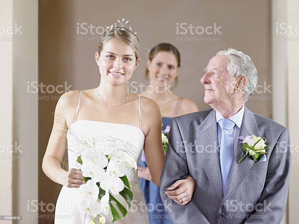 Bride with father and bridesmaid stock photo