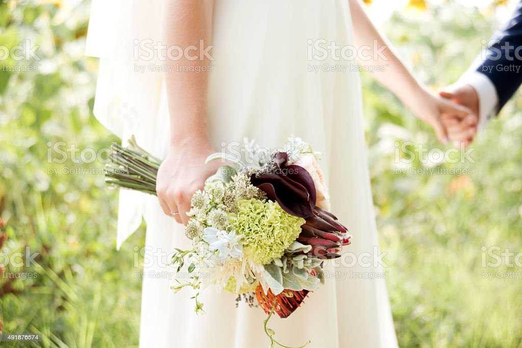 bride with flowers in the nature on wedding day stock photo