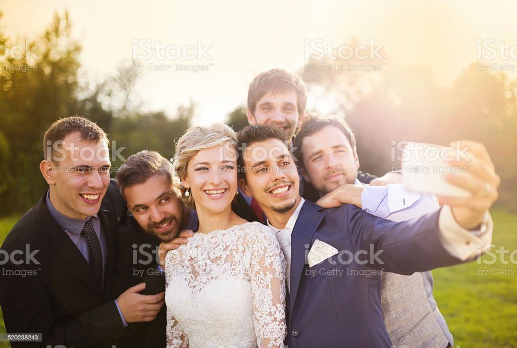 Bride with groom and his friends taking selfie stock photo