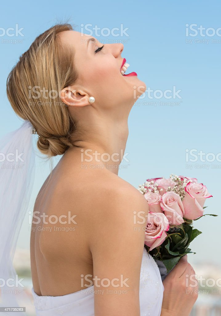 Bride With Her Head Back Holding Flower Bouquet Against Sky stock photo